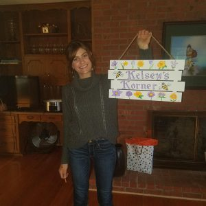 Head Gardener, Kelsey Jarvis, with her new office sign.